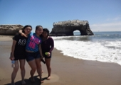 3 students pose in front of the natural bridge
