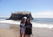 2 students pose in front of the natural bridge