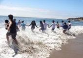 students hold hands and run into the ocean together