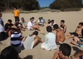 students sit in a big circle on the sand