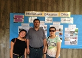 students pose in front of the international education office board