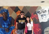2 students pose in front of a campus mural