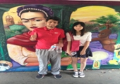 students take a photo in front of a colorful mural